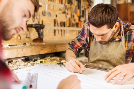 profession, carpentry, woodwork and people concept - two carpenters with ruler and blueprint at workshop