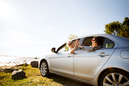 summer vacation, holidays, travel, road trip and people concept - happy teenage girls or young women in car at seaside making high five gesture Standard-Bild
