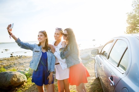 drive car: summer vacation, holidays, travel, road trip and people concept - happy teenage girls or young women with smartphone taking selfie near car at seaside Stock Photo