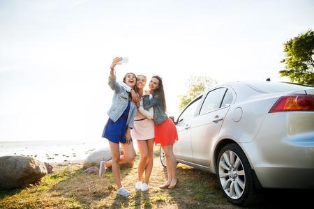 Vacaciones de verano, vacaciones, viaje, viaje por carretera y el concepto de la gente - adolescentes felices o mujeres jóvenes con teléfonos inteligentes teniendo autofoto cerca del coche en la playa Foto de archivo - 63325380