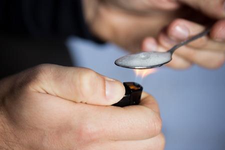 encendedores: el consumo de drogas, la delincuencia, la adicción, el abuso de sustancias y el concepto de la gente - cerca de adicto con dosis más ligero y cuchara preparación de crack en la calle