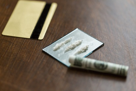 drug use: drug use, crime, addiction and substance abuse concept - close up of crack cocaine drug dose track on mirror with credit card and money