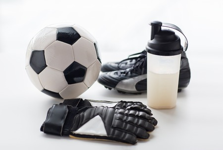 soccer boots: sport, soccer and sports equipment concept - close up of ball, football boots, goalkeeper gloves and protein shake bottle with drink