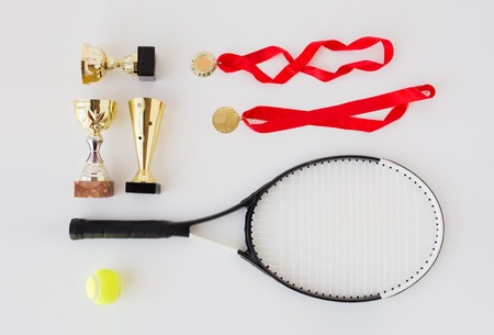 sport, achievement, championship, competition and success concept - close up of tennis racket and ball with cups and medals over white background Stock Photo