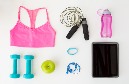 sport, fitness, healthy lifestyle, technology and objects concept - close up of tablet pc computer with sports stuff over white background