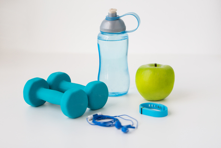 cardio fitness: sport, healthy lifestyle and objects concept - close up of dumbbells with fitness tracker, earphones, green apple and water bottle over white background