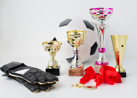 sport, achievement, championship and success concept - close up of football or soccer ball and goalkeeper gloves with golden medals and cups Stock Photo
