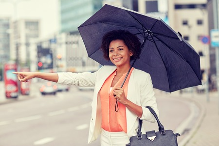 business trip, transportation and people concept - young smiling african american woman with umbrella catching taxi at city street