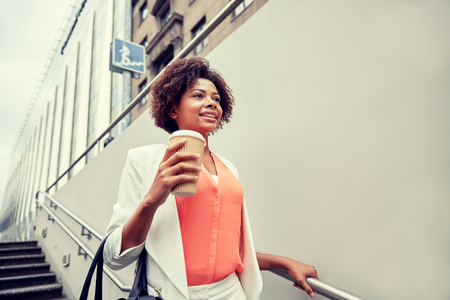 business and people concept - young smiling african american businesswoman with coffee cup going down stairs into city underpass Stock Photo