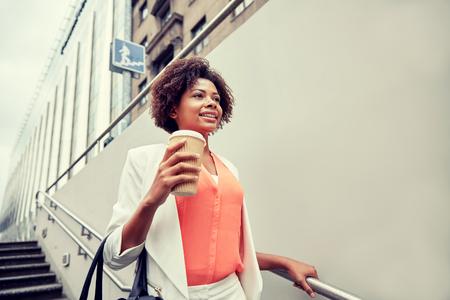 down stairs: negocios y concepto de la gente - joven sonriente africano americano de negocios con la taza de café bajando escaleras en paso subterráneo de la ciudad
