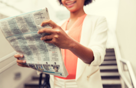 business, drinks, lifestyle and people concept - close up of young african american businesswoman reading newspaper walking downstairs to city subway