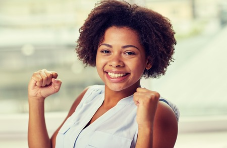 people, emotions, gesture and success concept - happy african american young woman with raised fists
