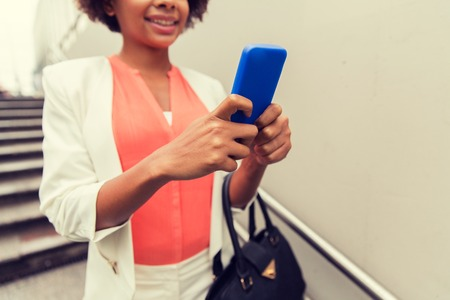 business, technology, communication and people concept - close up of young smiling african american businesswoman with smartphone and handbag texting walking downstairs to city subway Stock Photo
