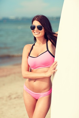resort beach: summer vacation, travel, surfing, water sport and people concept - young woman in swimsuit with surfboard on beach Stock Photo