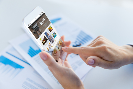 web screen: business, technology, media, internet and people concept - close up of woman hand holding and showing transparent smartphone with blog web page on screen at office Stock Photo