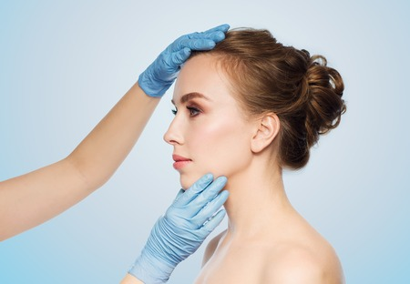 les gens, la cosmétologie, la chirurgie et la beauté plastique concept - chirurgien ou mains esthéticienne touchante visage de femme sur fond bleu