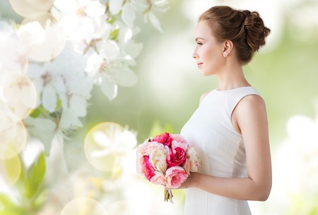 fiancee: holidays, wedding and people concept - bride or woman in white dress with flower bunch over natural spring cherry blossom background