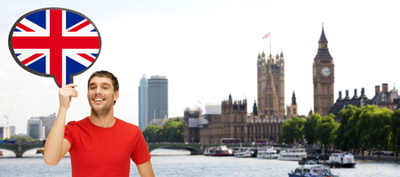foreign language, english, travel, people and communication concept - smiling young man holding text bubble of british flag over london city and big ben tower background