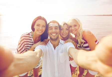 family vacation: summer, sea, tourism, technology and people concept - group of smiling friends with camera on beach photographing and taking selfie