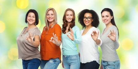 green clothes: friendship, fashion, body positive, gesture and people concept - group of happy different size women in casual clothes showing ok hand sign over green holidays lights background