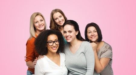 middle age women: friendship, fashion, body positive, diverse and people concept - group of happy different women in casual clothes over pink background Stock Photo