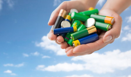 heap up: recycling, energy, power, environment and ecology concept - close up of hands holding alkaline batteries heap over blue sky and clouds background