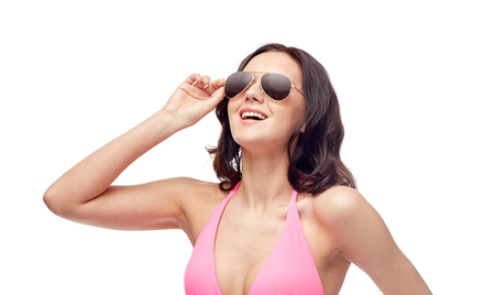 pink bikini: people, fashion, swimwear, summer and beach concept - happy young woman in sunglasses and pink bikini swimsuit Stock Photo