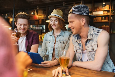 people, leisure, friendship and communication concept - group of happy smiling friends with tablet pc computer and drinks at bar or pub photo