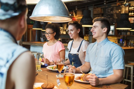 people, leisure, friendship and communication concept - group of happy smiling friends eating, drinking and talking at bar or pub photo