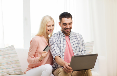 emoney: technology, people, e-money and commerce concept - smiling happy couple with laptop computer and credit or bank card shopping online at home
