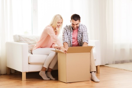 unpack: people, delivery, shipping and postal service concept - happy couple opening cardboard box or parcel at home