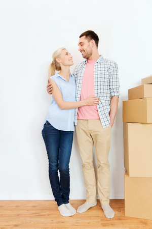 move in: home, people, repair and real estate concept - happy couple with many cardboard boxes moving to new place