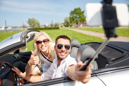 drive car: road trip, travel, couple, technology and people concept - happy man and woman driving in cabriolet car and taking picture with smartphone on selfie stick