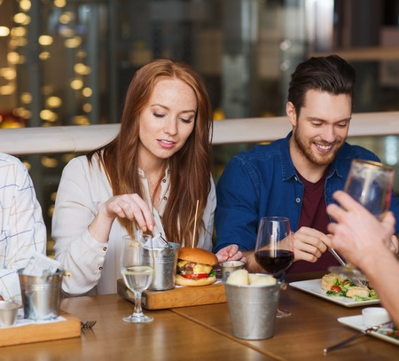 people   lifestyle: leisure, technology, lifestyle and people concept - happy man with smartphone and friends dining at restaurant