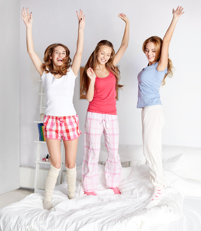 friendship, people and pajama party concept - happy friends or teenage girls having fun and jumping on bed at home Stock Photo