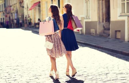 Verkauf, Konsum und Menschen Konzept - glückliche junge Frauen mit Einkaufstaschen entlang Stadt Straße Standard-Bild - 63311674
