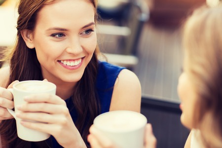 women smiling: communication and friendship concept - smiling young women with coffee cups at cafe