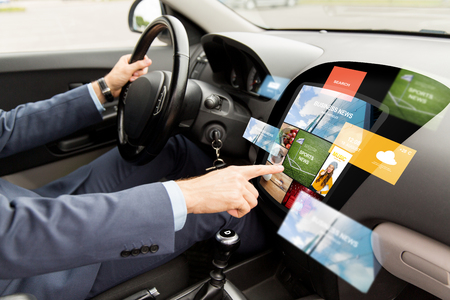 transport, modern technology, business, media and people concept - close up of man driving car with news on board computer screen Banco de Imagens
