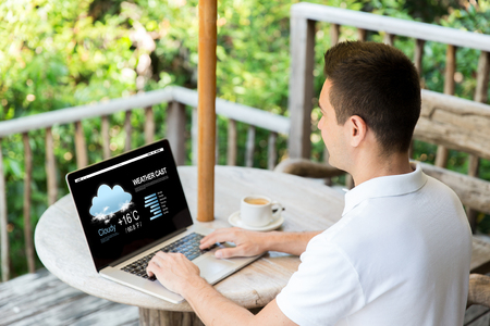 laptop home: business, weather cast, people and technology concept - close up of businessman at laptop computer with meteo forecast on screen outdoors on summer terrace and drinking coffee