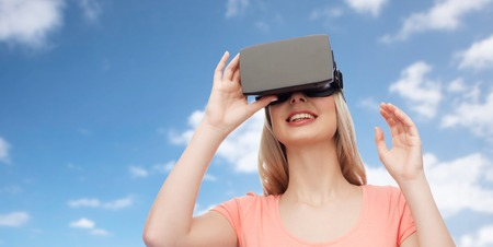 technology, virtual reality, entertainment and people concept - happy young woman with virtual reality headset or 3d glasses over blue sky and clouds background Stock Photo