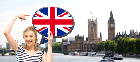 british english: foreign language, english, travel, people and communication concept - smiling woman holding text bubble of british flag and pointing finger over london city and big ben tower background