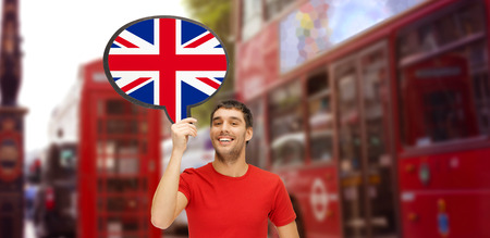 foreign language, english, travel, people and communication concept - smiling young man holding text bubble of british flag over london city street background