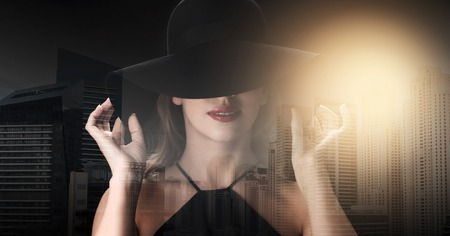 femme fatale: people, luxury and fashion concept - beautiful woman in black hat over dark over dubai city background with double exposure and highlight