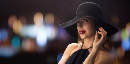 femme fatale: people, luxury and fashion concept - beautiful woman in black hat over blurred night lights background