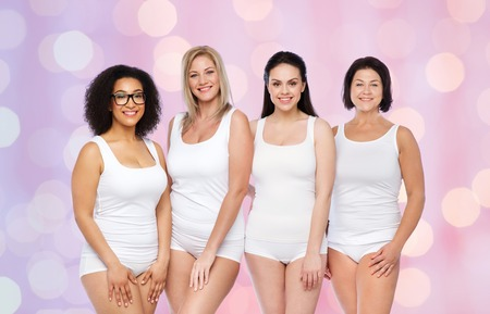 friendship, beauty, body positive and people concept - group of happy women different in white underwear over rose quartz and serenity lights background Stock Photo