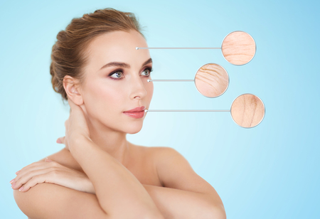 aging woman: beauty, people, aging and skin care concept - beautiful young woman and circles with magnified facial wrinkles over blue background