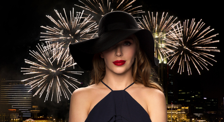 femme fatale: people, luxury and fashion concept - beautiful woman in black hat over night singapore city and firework background