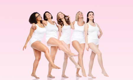 friendship, beauty, body positive and people concept - group of happy women different in white underwear over pink background 스톡 콘텐츠
