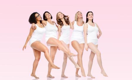 vriendschap, schoonheid, lichaam positieve en mensen concept - groep van gelukkige vrouwen verschillend in wit ondergoed over roze achtergrond Stockfoto