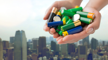 heap up: recycling, energy, power, environment and ecology concept - close up of hands holding alkaline batteries heap over singapore city skyscrapers background